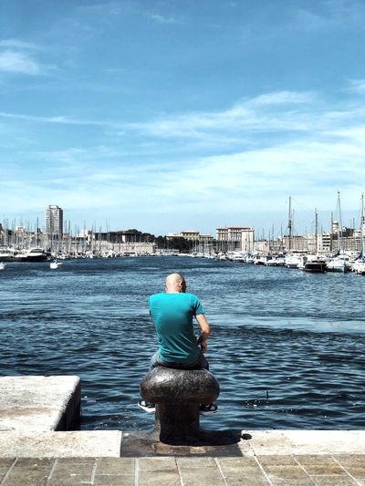 Rear view of man looking at sea against cityscape
