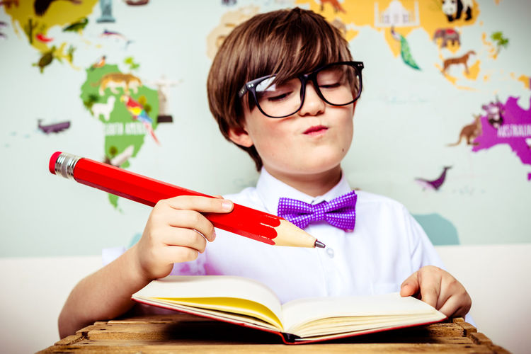 Close-up of cute boy holding large pencil with book at table