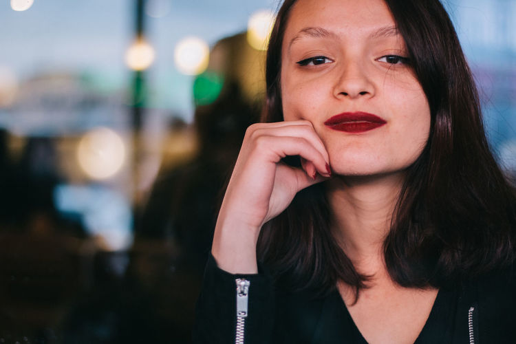 Close-up of young woman touching cheek sitting at restaurant