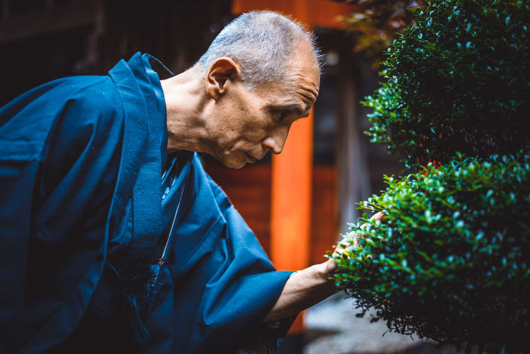 Side view of man looking at plants