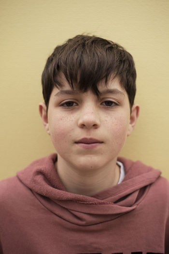 Portrait of boy against yellow background