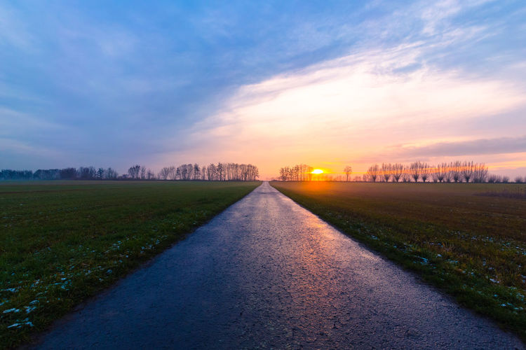 Surface level of road amidst field against sky during sunset