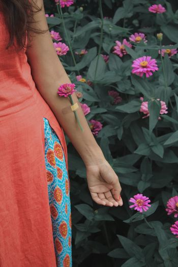 Midsection of woman standing by pink flowering plants