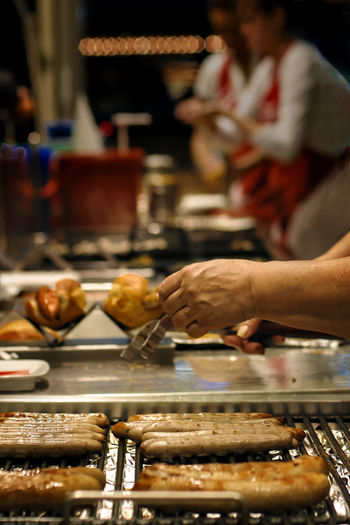 Cropped image of worker by sausages on barbecue grill at store