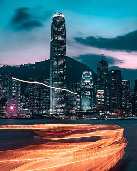 Illuminated modern buildings against sky in city