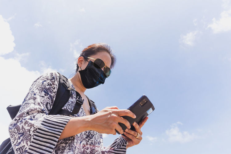 Low angle view of woman holding mobile phone against sky