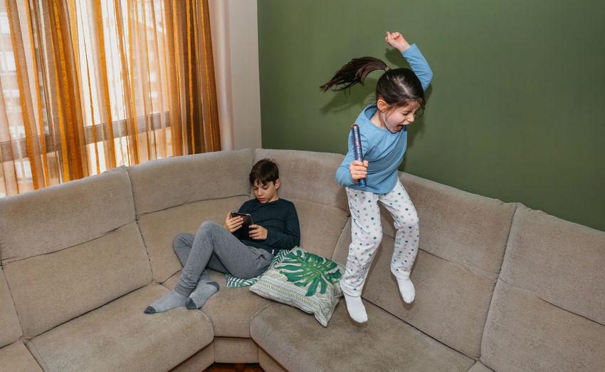 Full length of girl jumping on sofa at home