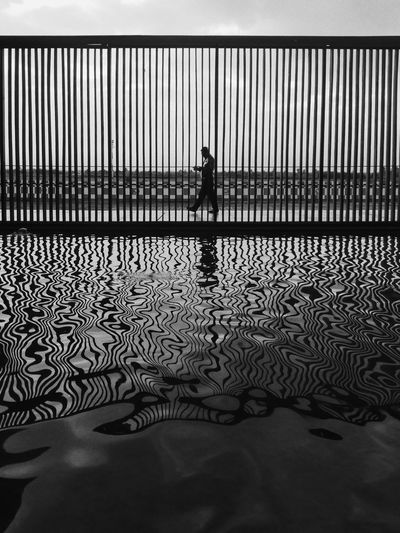 Side View Of Silhouette Man Walking By Lake With Fence Reflection