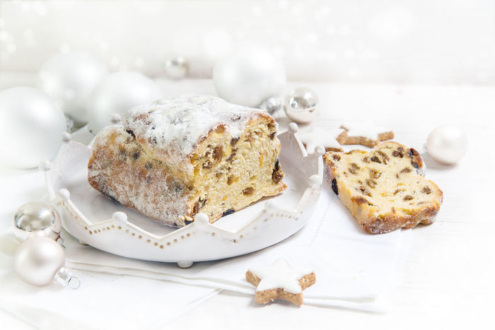 German Christmas cake, called criststollen with raisins and candied fruit on a white plate, decorated with bright Christmas balls and cinnamon stars on a white table, copy space Advent Holiday Cake Christstollen Cristmas Day Decoration Food Food And Drink Freshness Indoors  No People Plate Ready-to-eat Silver  Stars Sweet Food Table White