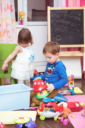 Siblings playing with toys at home