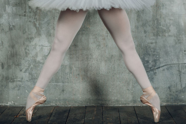 Low section of woman in ballet shoe dancing on floorboard