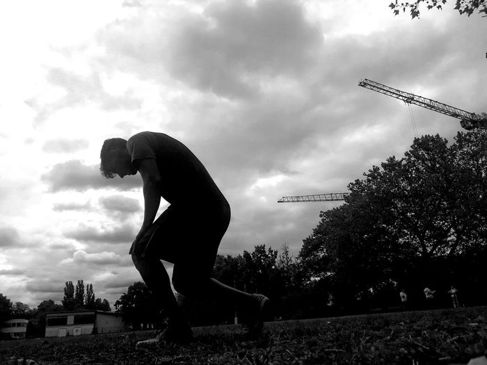 Side view of silhouette man playing soccer against sky