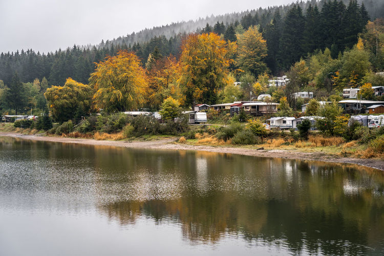 Scenic view of lake by trees and houses during autumn