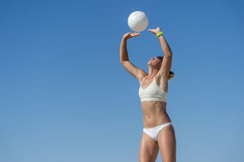 Low angle view of woman playing with ball against clear blue sky
