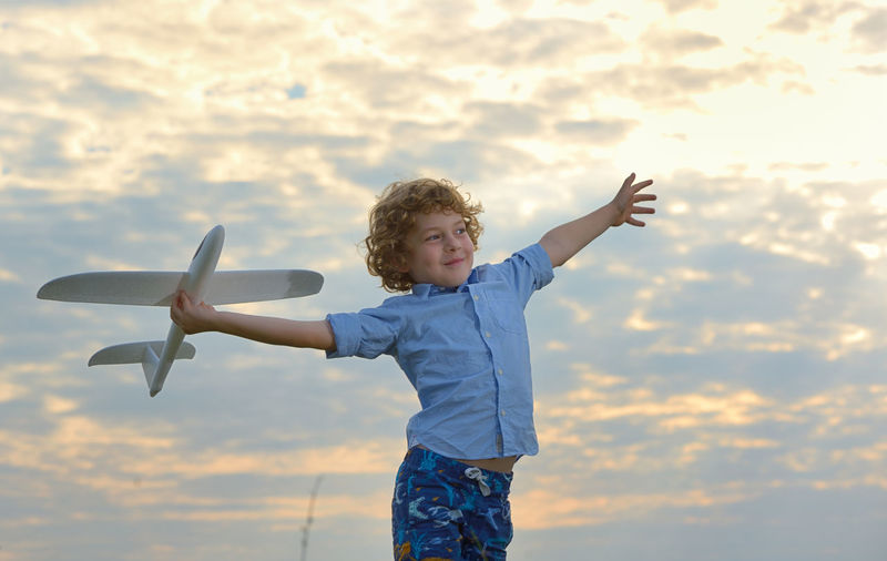 Boy holding toy airplane against sky during sunset
