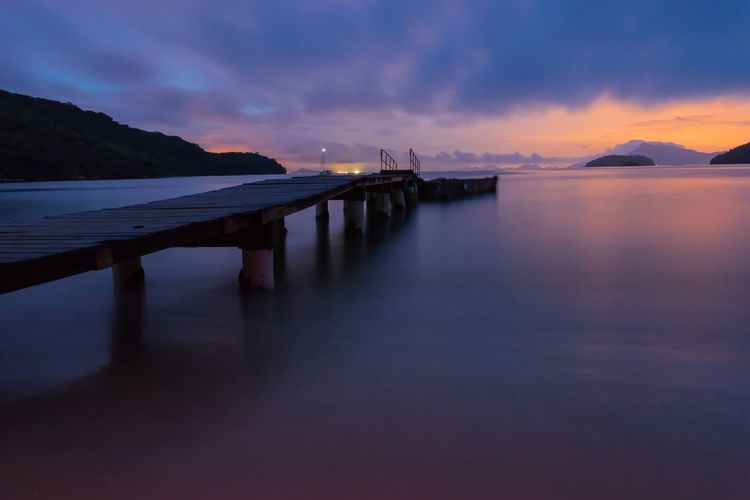 Pier over sea against dramatic sky