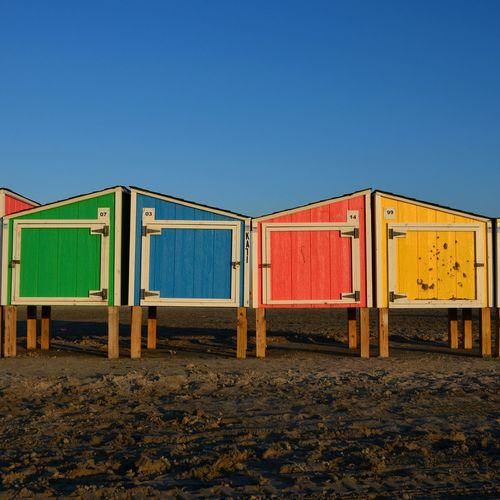 Multi Colored Wooden Lockers On Beach Against Clear Blue Sky