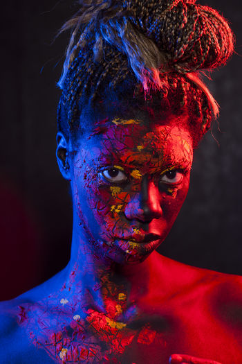 Close-up portrait of shirtless young woman with powder paint on face