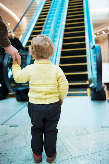Rear view of cute girl standing by escalator at mall
