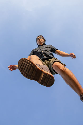 Low angle view of person jumping against blue sky