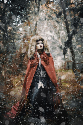 Young woman wearing cape during snowfall in forest