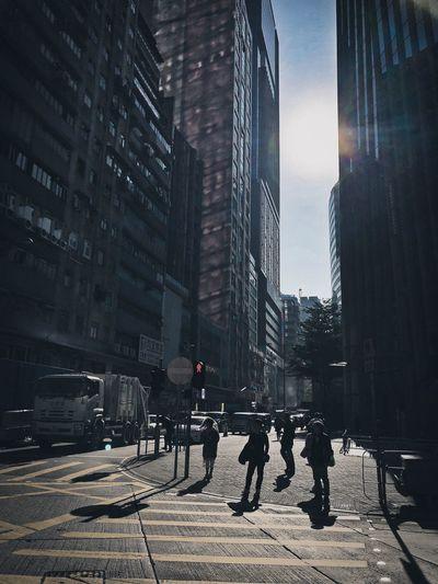 Silhouette people on sidewalk amidst buildings in city