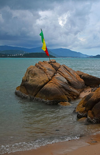 Rasta flag standing abobe sea stone under stormy sky, fisherman's village, Koh Samui, Thailand Flag Koh Samui PanAfricanFlag Protest RASTA Rastafari Rock - Object Sea Sea And Sky Sea_collection Shore Stone Storm Clouds Stormy Weather Thailand Vivid Water Landscapes With WhiteWall Spotted In Thailand The KIOMI Collection Blue Wave