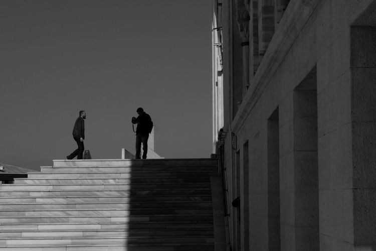 Silhouette men on staircase against sky