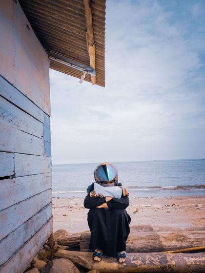 Full length of woman wearing helmet sitting against sea