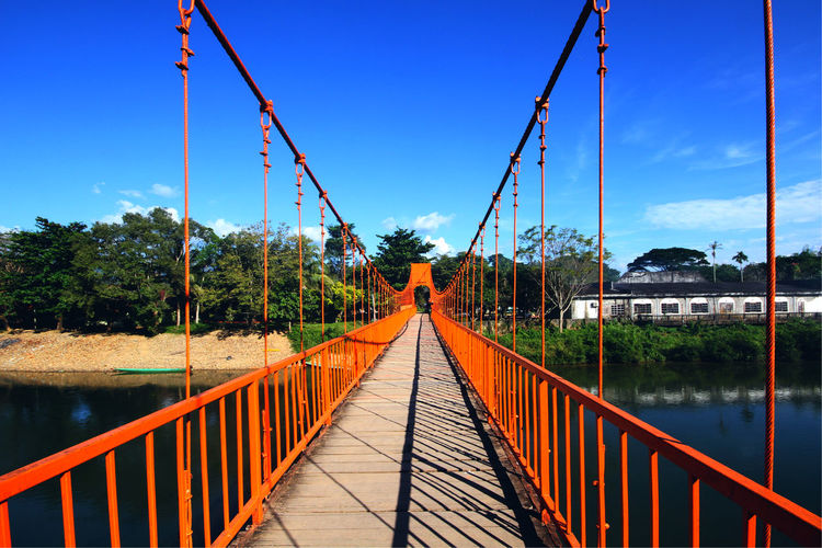 Orange steel bridge across on the river and mountain at countryside of Vangvieng,Laos Vangvieng,Laos Architecture Bridge Bridge View Built Structure Connection Countryside Day Diminishing Perspective Direction Footbridge Nature Outdoors Plant Railing River Side Sky Steel Bridge The Way Forward Transportation Tree Water