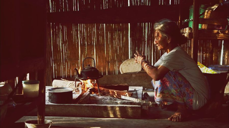 Woman preparing food on stove in hut