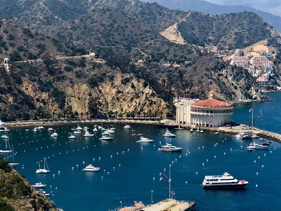 Catalina Island, A view over looking Catalina Bay located in the waters of Southern California. Deep Blue Ocean water surrounded by mountains / desserts Eye Em New Here Structure And Nature Bright Day Daylight Boats Docked On The Water Deep Blue Ocean Catalina Bay Catalina Island, Avalon, California Catalina Mountains  Catalina Island  Water Nautical Vessel Mountain Architecture Built Structure Nature Tree Day Sea No People Sailboat Outdoors Travel Beauty In Nature High Angle View EyeEmNewHere