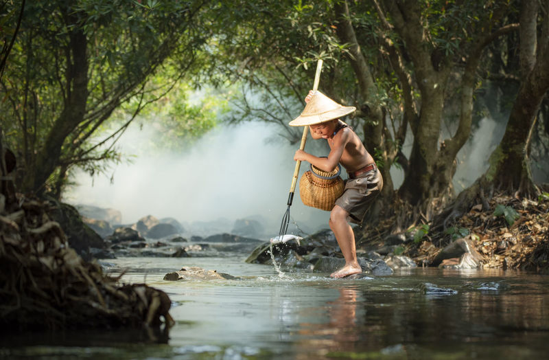Boy catching fish while standing by river in forest