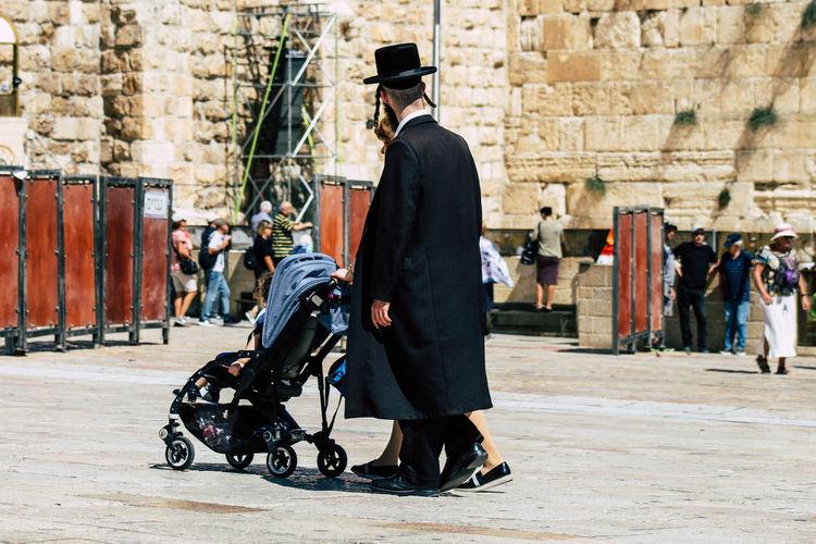 Side view of men walking in city