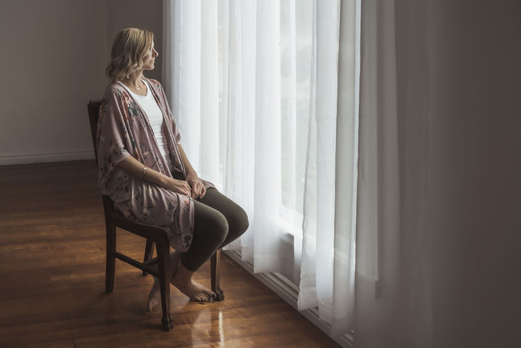 Woman sitting by window at home