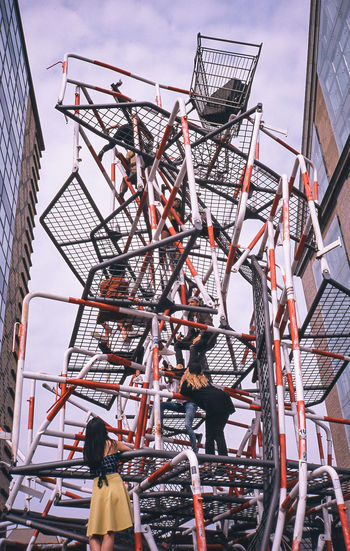 Low angle view of people on metal structure against sky