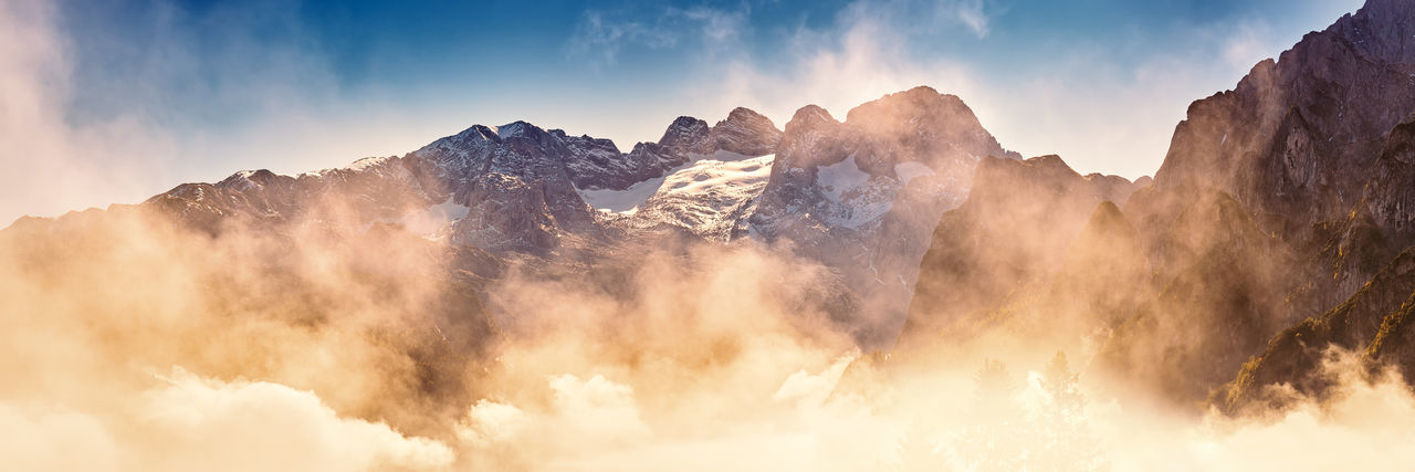 Panoramic view of majestic mountains against sky during sunset