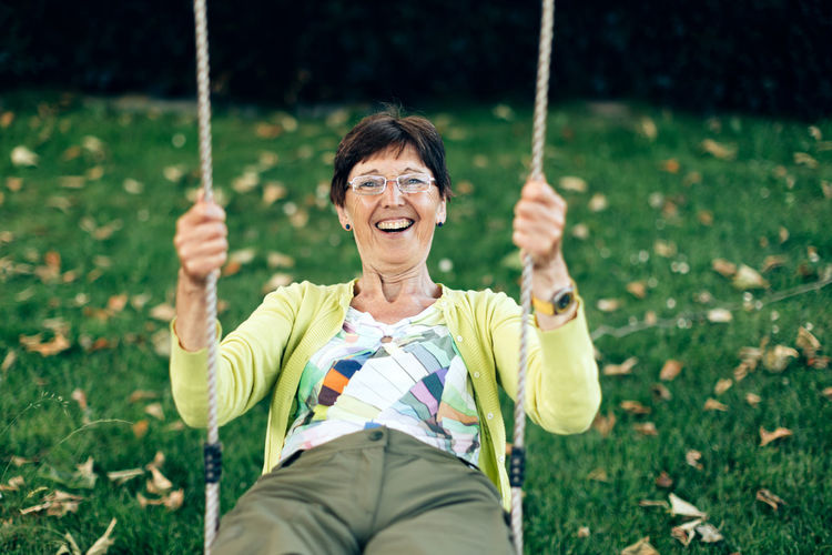 Positive smiling healthy elderly woman plays on the swing