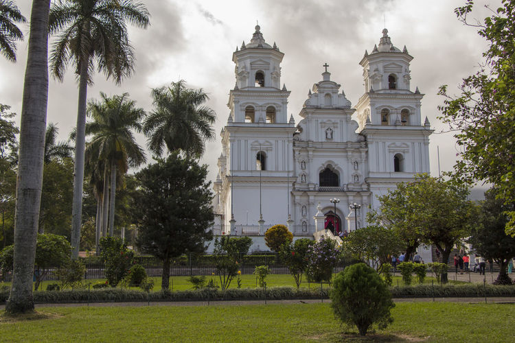 Architecture Building Exterior Built Structure Church Cloud Cloud - Sky Day Esquipulas Exterior Façade Famous Place Footpath Green Color Growth Guatemala History In Front Of Outdoors Palm Tree Place Of Worship Religion Sky Spirituality Tourism Travel Destinations