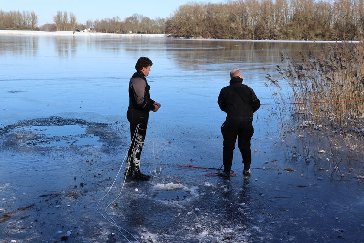 Rear view of men standing on lake during winter