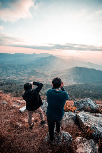 Rear View Of Friends Photographing Through Camera While Standing On Mountain Against Sky During Sunset