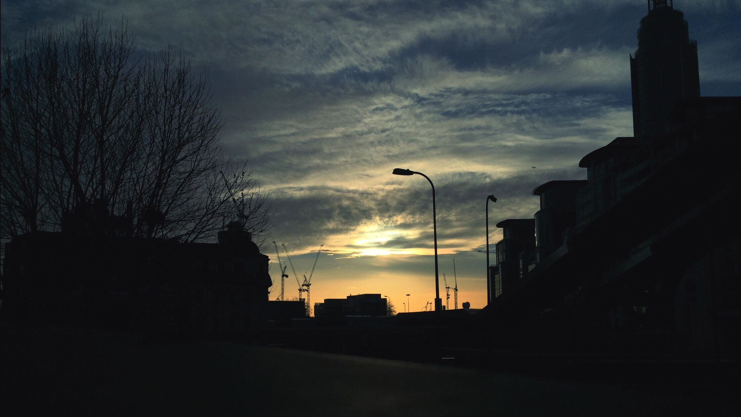 architecture, silhouette, building exterior, built structure, sky, sunset, cloud - sky, street light, dusk, dark, city, low angle view, cloudy, cloud, building, street, outdoors, road, no people, residential structure