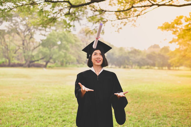 Young Woman In Graduation Gown Playing With Certificate While Standing On Grassy Field At Park