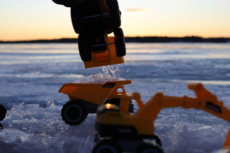 Close-up of toy car on snow covered land during sunset
