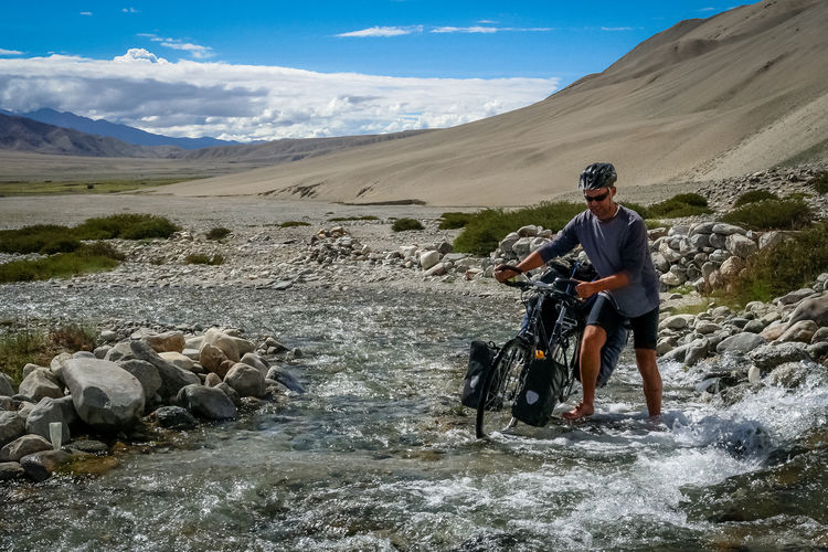 Man riding bicycle on river against sky