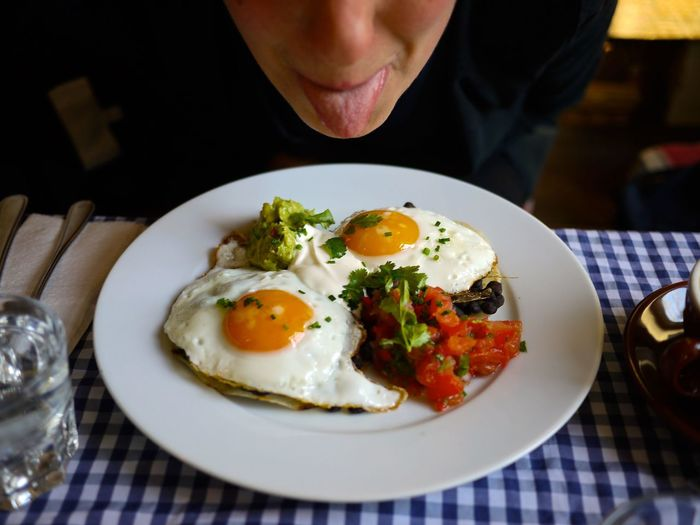 Young woman sticking tongue out while sitting on brunch eggs in plate on table