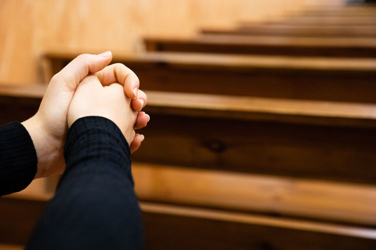 Cropped hands of woman praying in church