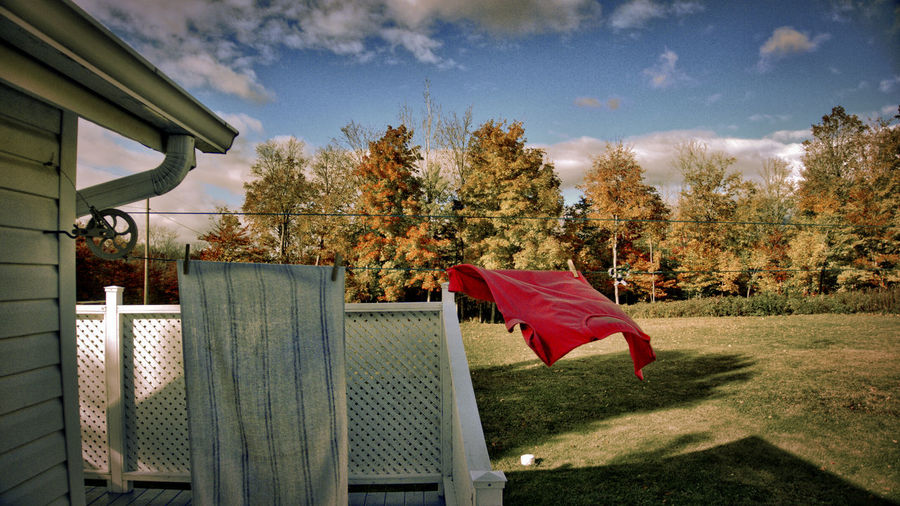 Close-up of clothes drying on clothesline against sky