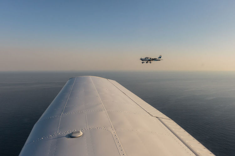 Airplane flying over sea against clear sky