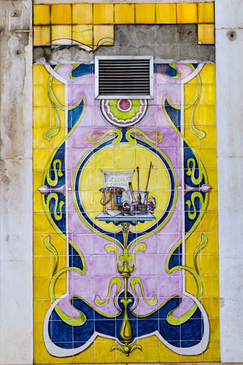 Colourful decorative tiles on external fascia of building, somewhat defaced by air vent. Colourful EyeEm Selects Architectural Feature Architecture Built Structure Close-up Day Decorative Art Defaced No People Outdoors Tiles Yellow